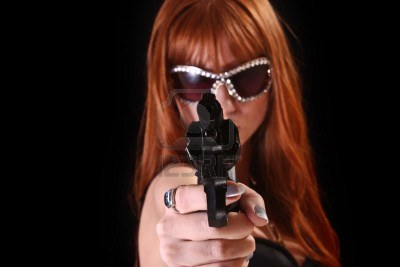 6187583-young-redhead-woman-with-gun-on-black-background